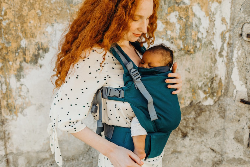mother holds baby in hip healthy baby carrier position